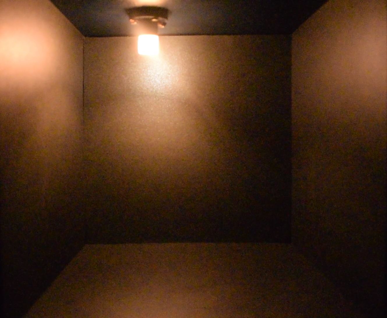 Trauma by artist Priti Patel is a piece of conceptual art. It is a model empty square room showing a light flashing Help in Morse code