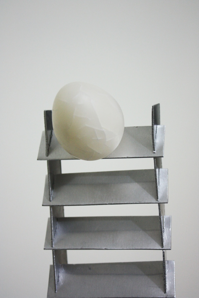 Close up of On the Verge sculpture by artist Priti Patel. It shows a fragile translucent cracked egg, made from cernit polymer clay, standing at the top of a twisted aluminium stair case that is tapered. The staircase is standing in a square pool of black oil.